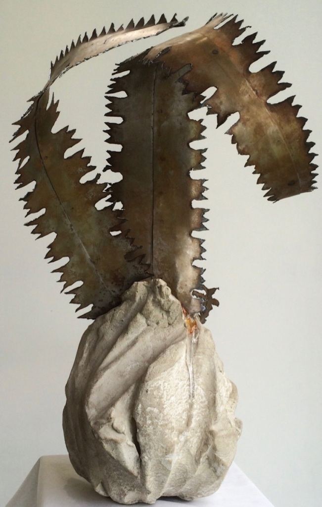 Detailed view. DiNA Metal fern like shoots sprouting from seedpod form which appears to be made from stone.