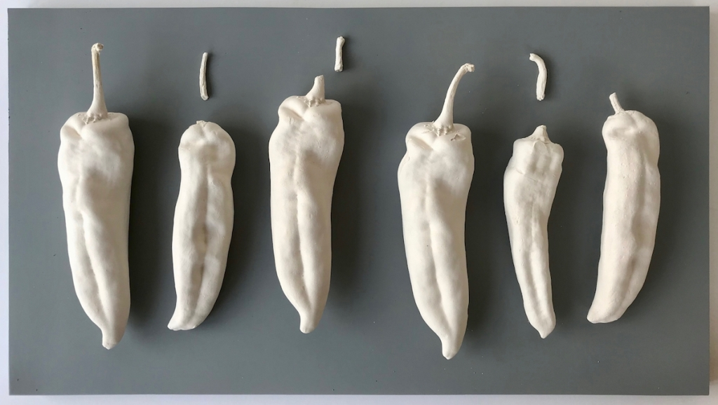 Fragmented Order - six large white ceramic Chilli peppers arrange in order across grey base board.