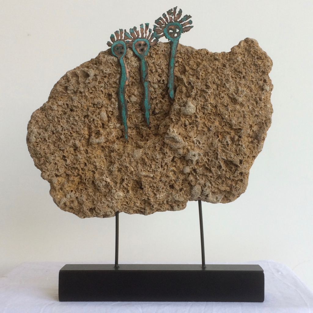 A piece of fossiliferous limestone, Coraline Crag is mounted on two rods. Three copper Spirit figures emerge from the rock.