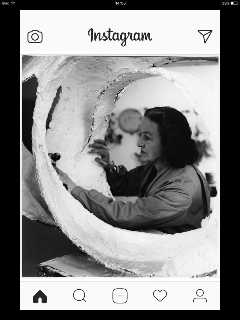 Instagram screenshot of post showing Barbara Hepworth at work - her head iand upper torso in centre of hollow curved form she is making in plaster.
